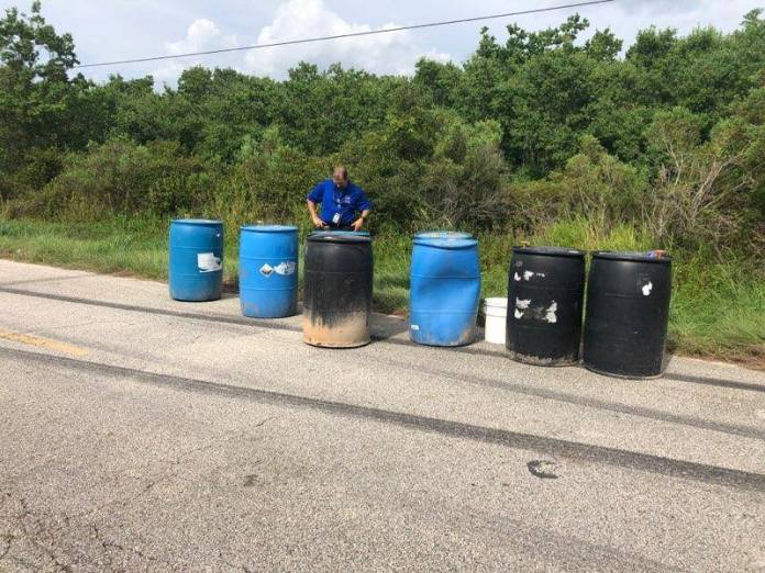 Precinct 4 Constable's Office investigators, Harris County Pollution Control and an environmental clean up company, handle eight barrels of acid (approximately 200 gallons) dumped on the road. (Precinct 4 Constable's Office photo)