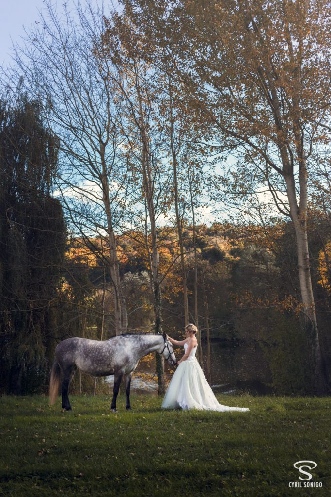 Mariée avec son cheval réalisant une séance de portrait fineart par le photographe de mariage Cyril Sonigo