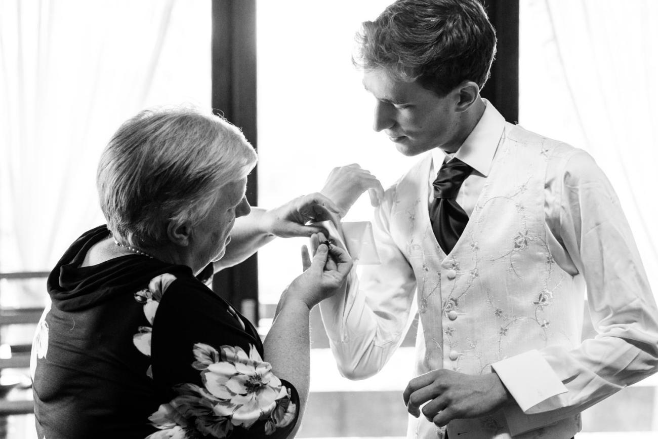 Préparatifs du marié en présence de sa mère qui l'aide à mettre ses boutons de manchette