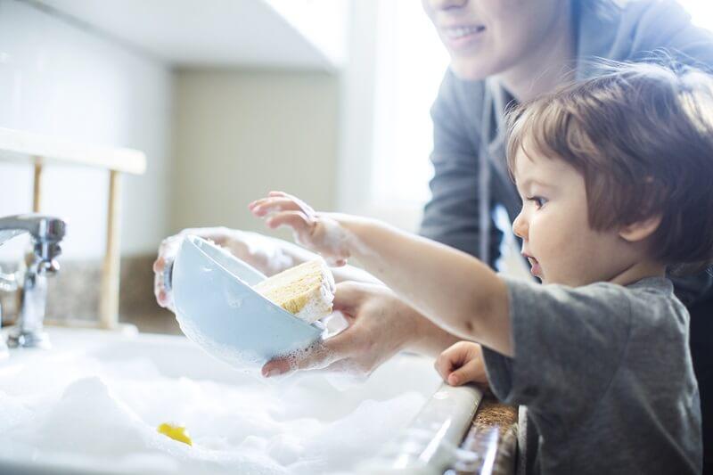 Fotografija udomljenog djeteta koje se igra sa udomiteljicom perući svoju zdjelicu