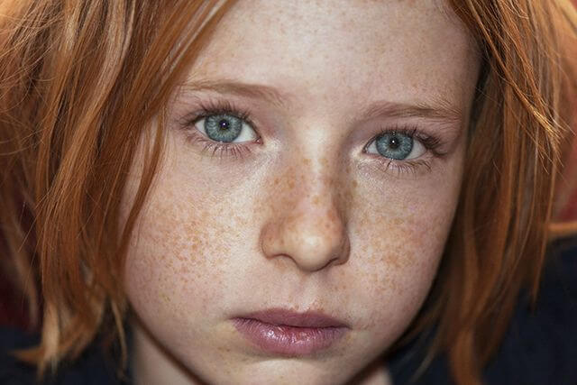 Fotografija glave lijepe crvenokose pjegave djevojčice sa izraženom tugom u očima