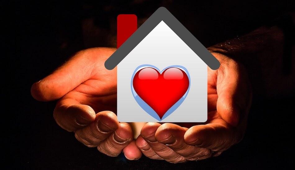 Na slici su spojeni dlanovi na koje je smješten simbol kuće sa srcem u sredini