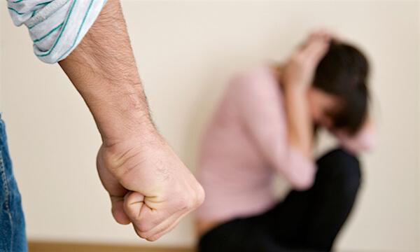 Nasilje u obitelji - U prednjem planu slike vidi se dio muške ruke sa stisnutom šakom. U pozadini je sklupčana ženska osoba koja glavu štiti rukama.