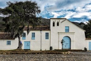 Color photograph of a colonial-era church in Salento, Colombia. The church is painted white, with blue doors and sits in a cobblestone plaza.