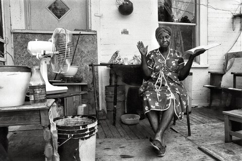 Black and white photograph of an elderly African American woman sitting on a cluttered porch, holding up a Bible in her left hand and holding up her right hand as if testifying.