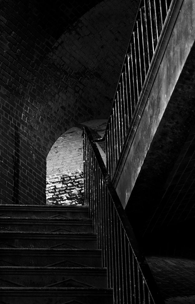 Black and white photograph looking up an iron staircase.