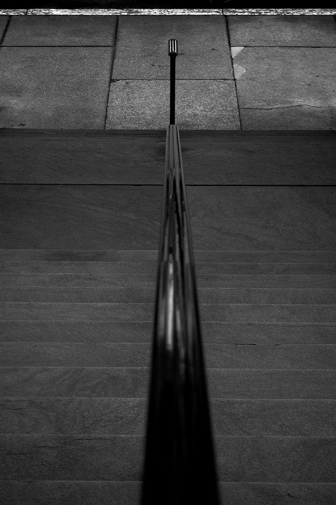 Semi-abstract black and white photograph looking down an iron rail toward the sidewalk.