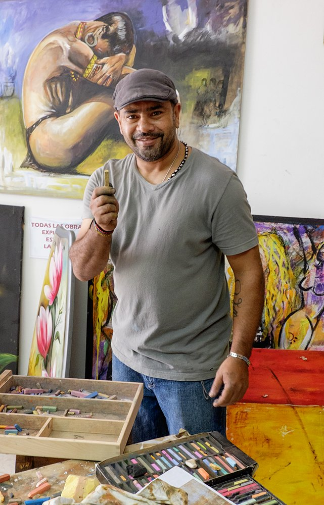 Color photograph of a latino artist in his studio.