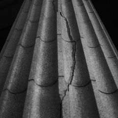 Black and white photograph looking up a cracked buildingn column.