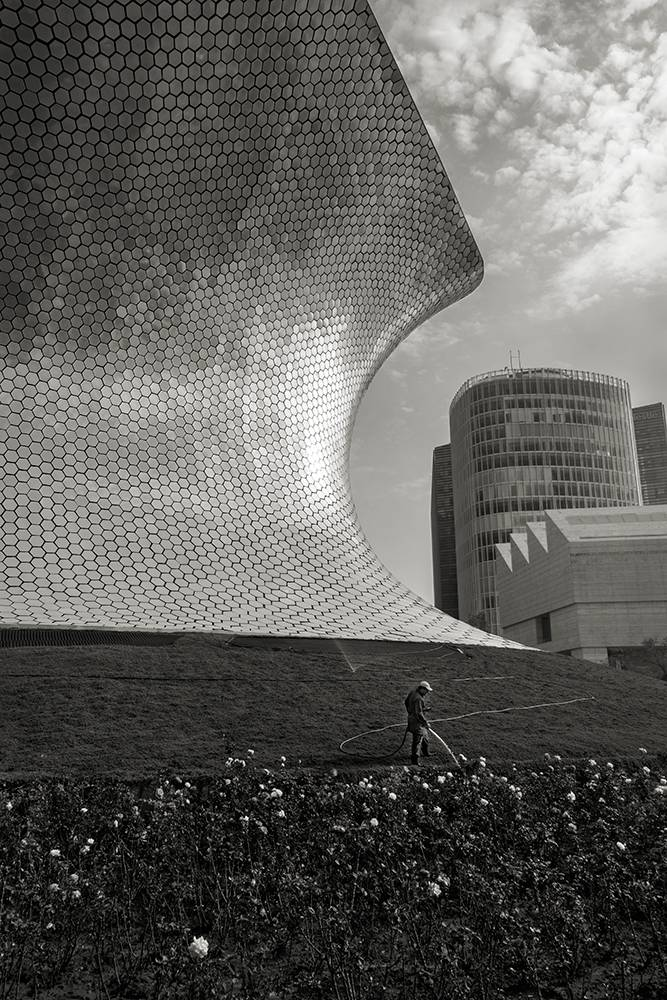 Black and white photo of a modern building shaped like an hourglass.