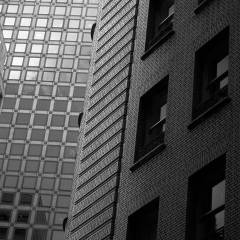 Black and white photograph looking up the side of an old brick building.