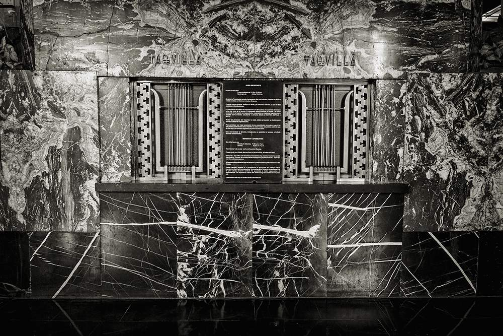 Black and white photo of a marble, art deco ticket office at a theatre.