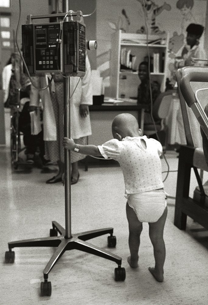 Black and white photo of a toddler in a diaper pushing a machine that administers chemotherapy drugs.
