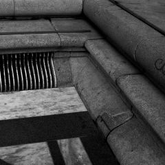 Black and white photograph of marble tiles leading to a antique storm drain grate.