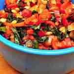 A blue bowl of multicolored cooked and chopped Swiss Chard | Swiss Chard Sauteed With Pine Nuts and Raisins
