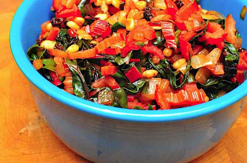 A blue bowl of multicolored cooked and chopped Swiss Chard | Swiss Chard Sautéed With Pine Nuts and Raisins