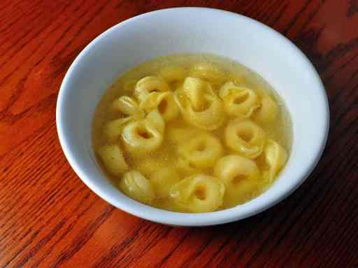 A white bowl with tortellini in broth on a reddish-brown wood background