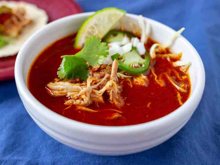 Bowl of Mexican Chicken Soup in Red Chile broth, with shreds of chicken, cilantro leaves, jalapeno slices, and diced onion on top
