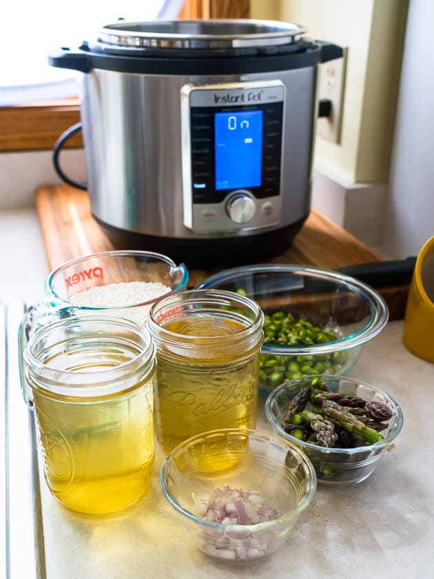 Bowls and cups of shallots, asparagus tips, vegetable broth, and rice in front of a pressure cooker