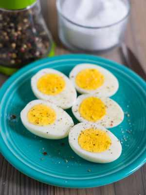 Halved hard-boiled eggs on a teal plate, sprinkled with salt and pepper, with a pepper grinder, salt pig,and paring knife in the background