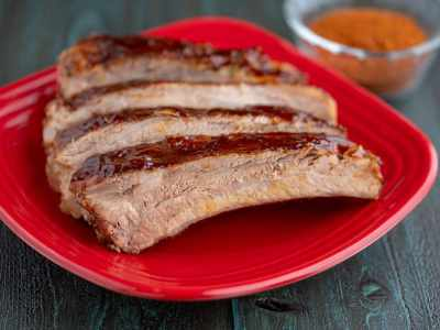 Individual spare ribs brushed with sauce on a red plate with a bowl of barbecue rub in the background