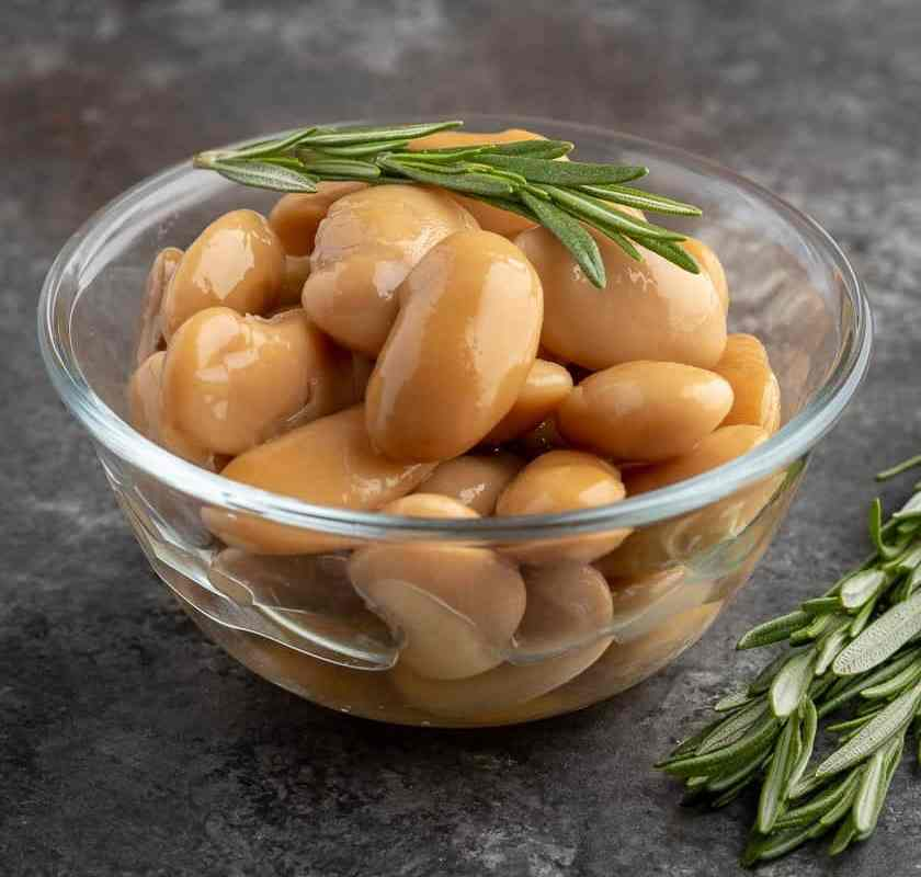 A bowl of cooked royal corona beans with a sprig of rosemary on top and on the table next to them.