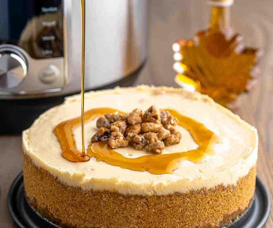 A cheesecake with maple syrup being drizzled on it, with an Instant Pot and a bottle of maple syrup in the background.
