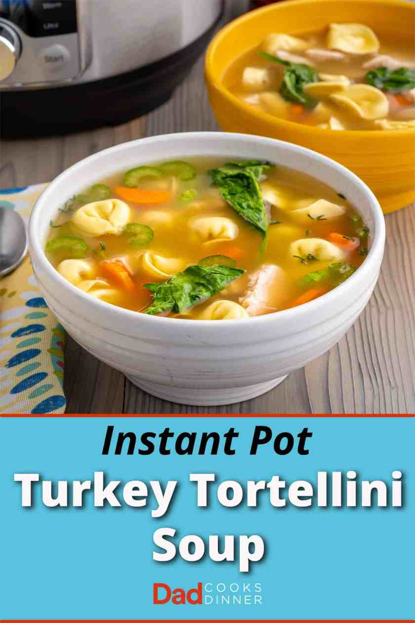 A bowl of turkey tortellini soup with carrots, spinach, tomatoes, and celery, with an instant pot visible in the background