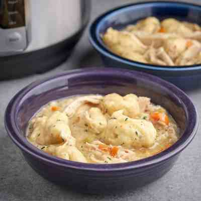 Two bowls of chicken and dumplings, with an Instant Pot in the background, on a gray table