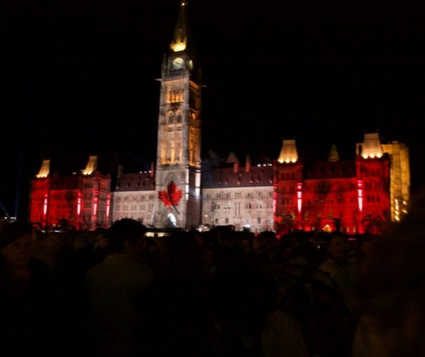 Image of Canadian Parliament Buildings at night with a Canadian flag projected on the building