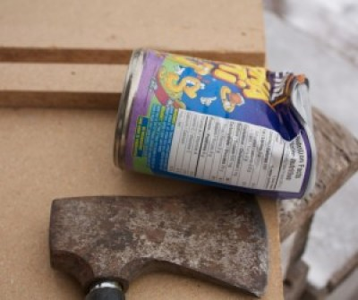 Image of a can dented by a hatchet