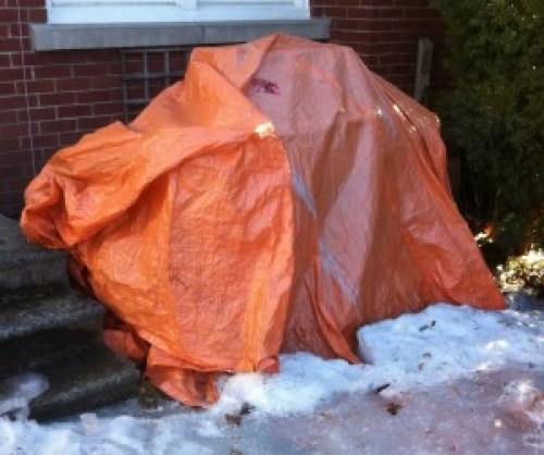 Image of a BBQ covered by a tarp frozen to the ground.
