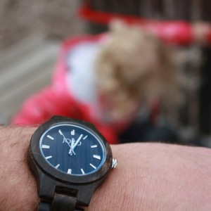 Image of a Wooden Jord Watch with a child running up stairs in the background