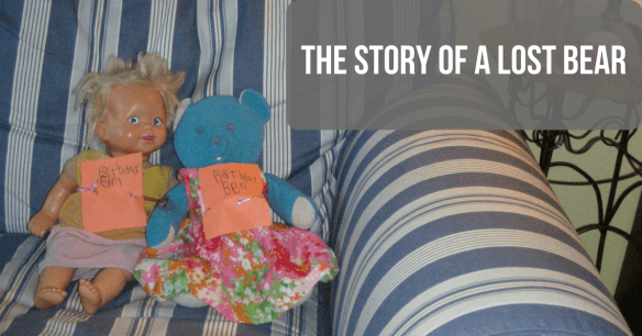 Image of a blue bear and a doll sitting together on a couch