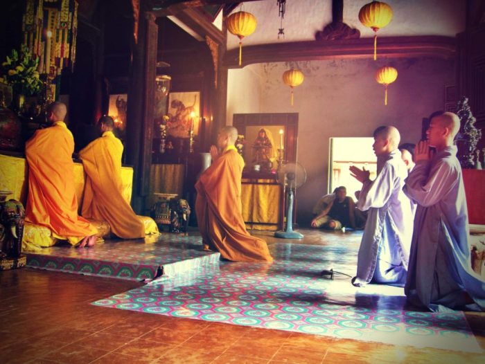 the Buddhist monks are praying the hall of the buddhist temple, figures of bodhisattvas and people watching are in the background