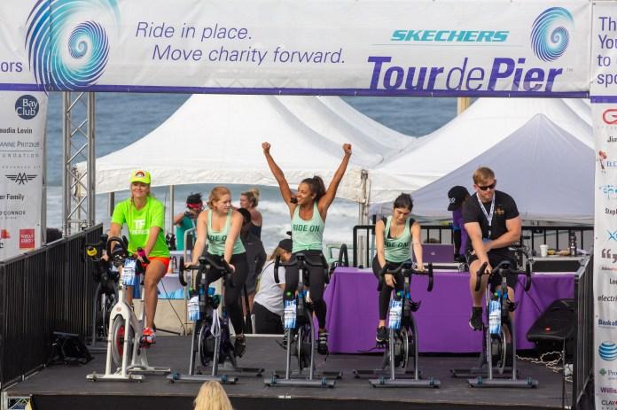 Bike riders walk around for cancer causes at the Tour de Pier in Manhattan Beach