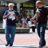 David Temple, left, distributes fliers on Sproul Plaza. Temple had predicted the world would end last Saturday.