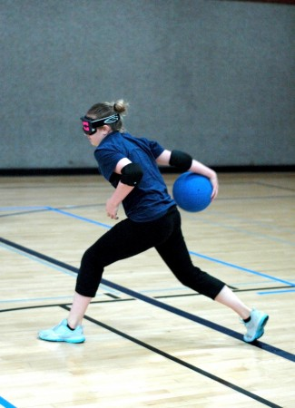 Goalball player makes a pass. Notice the eyeshades.
