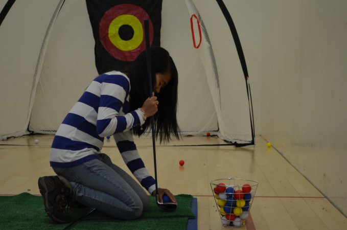 Anne Kwong, Internal President for the Disabled Students Union, adjusts the golfing tee