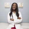 Dr. Nadine Burke Harris poses in her white coat, in a medical examination room.