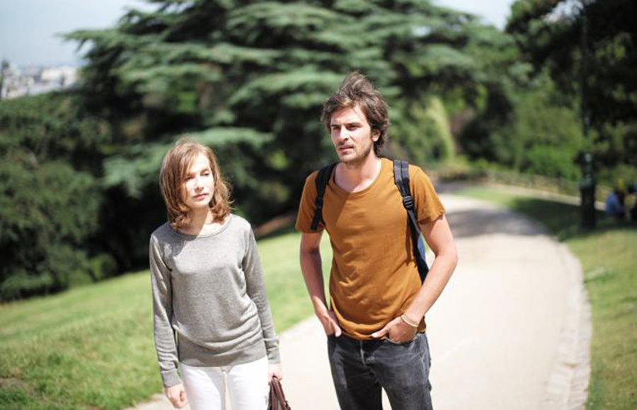Two people standing in the middle of a path that runs through a green park. Their expressions look blank and dismayed and the background appears to be blurred as if in motion while they are pictured clearly.