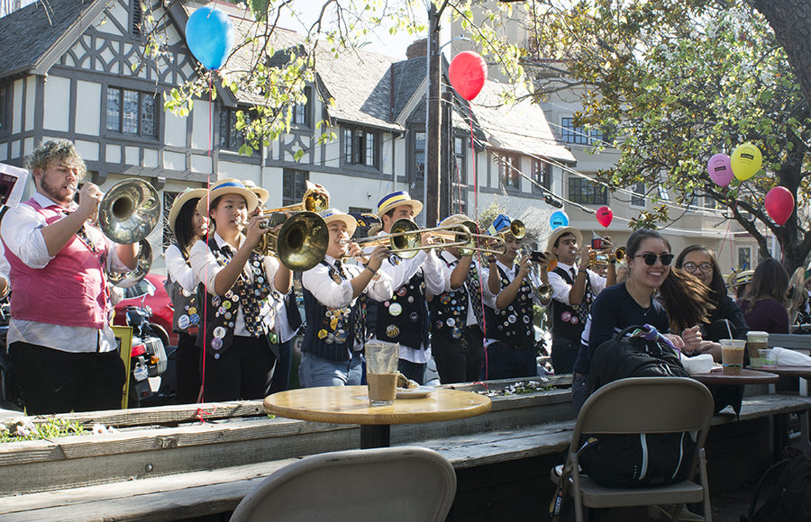 Marching band plays outside of a cafe on a sunny day.