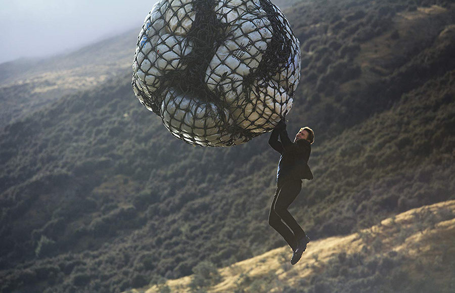 A man hangs from a large circular package in the sky.
