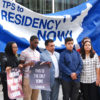 """A group of teens and young adults of color stand with an older man in front of a large banner with the words """"TPS to Residency NOW!"""" printed on top of a graphic of the United States. The youth hold sings saying """"This is the only home I know""""."""