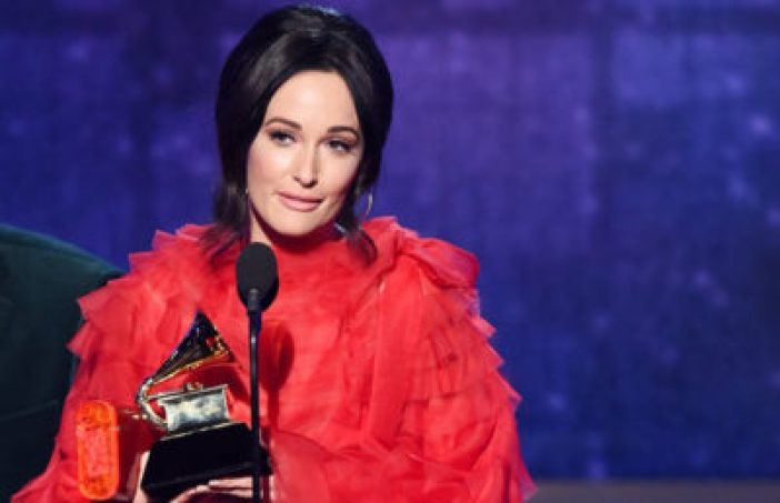 Woman in glamorous red gown speaks into microphone holding a Grammy award.