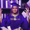 A man in a purple graduation cap and gown and flashy accessories throws papers into the air while sitting in front of a bookshelf.