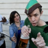Man dressed in green costume holding a beer bottle looks and points into camera while leaning in as other people in costumes hold him back.