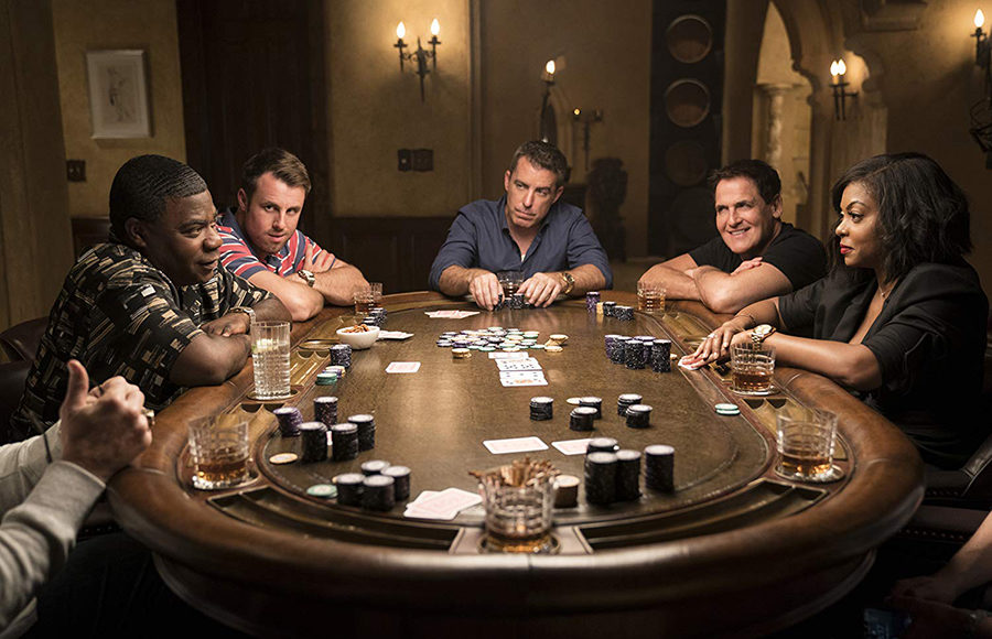 A group of people sitting around a poker table.