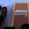 """Students crowding around door with sign that reads """"On sabbatical"""" with the word """"Suspended"""" crossed out"""