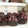Chocolate cupcakes with pink heart sprinkles sit on a cupcake stand.